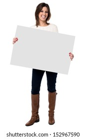 Attractive happy young woman with a friendly smile holding a blank white sign with copyspace for your text or advertisement
