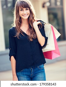 Attractive happy young woman shopping at the mall