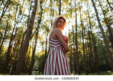 Attractive happy young woman in a stylish pink striped sundress with a sweet smile relaxes outdoors. Cheerful girl rest among the trees in the forest and enjoys the bright summer sun.