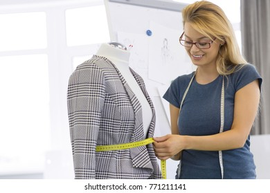 Attractive happy young woman working at her steelier designing clothing making measurements on a mannequin sewing designer style profession tailor atelier workshop crafting creativity businesswoman