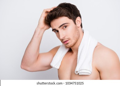 Attractive, harsh, virile, flirty, stunning, manly, confident, sportive macho with flawless, smooth, soft skin combing, touching his perfect hair with hand, looking at camera over white background
