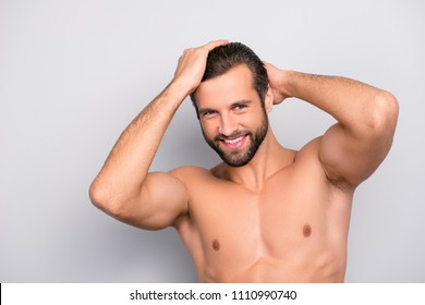 Attractive, harsh, virile, flirty, stunning, manly, confident, sportive macho with flawless, smooth, soft skin combing, touching his perfect hair with two hands, looking at camera over gray background