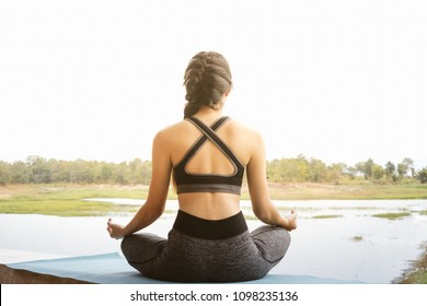 Attractive Healthy Asian Woman doing yoga sitting in the lotus position by the park