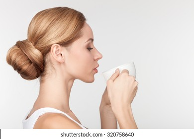 Attractive healthy blond girl is drinking coffee. She is standing in profile. The lady closed her eyes with enjoyment. Isolated and copy space in right side