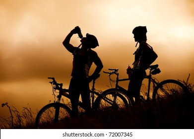 Attractive, healthy couple drink from their water bottles on mountain bikes, silhouette at sunset. active outdoor lifestyle concept