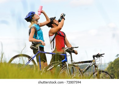 Attractive, healthy couple drink from their water bottles on mountain bikes. active outdoor lifestyle concept