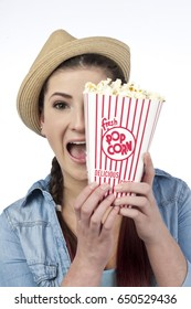 Attractive healthy looking young caucasian women eating popcorn; isolated on white background
