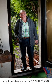 attractive healthy male senior with white hair and blue eyes in leisure wear with cardigan, checkered shirt and jeans comes in from the garden through an opened door, he looks friendly and satisfied