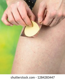 Attractive healthy woman applying a nicotine patch on her thigh