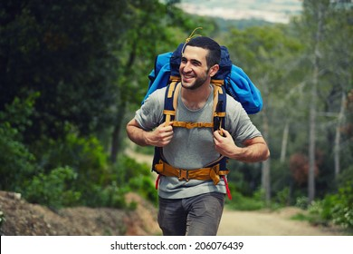 Attractive hiker with big traveling rucksack moving up on the mountain trail and smiling, happy traveler overcome big way smiling looking away, adventure travel and discovery
