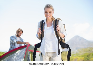 Attractive hiking blonde smiling at camera while partner pitches tent on a sunny day