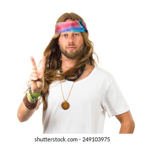 Attractive hippie giving a peace sign isolated on white