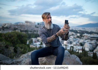Attractive hipster with a beard is sitting on a rock high over Athens City with Acropolis view and makes a selfie
