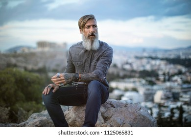 Attractive hipster with a beard is sitting on a rock high over Athens City with Acropolis view