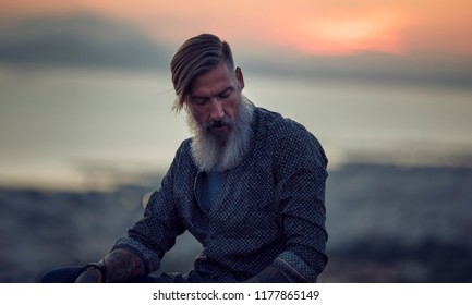 Attractive hipster with a beard is sitting on a rock high over Athens City at sunset