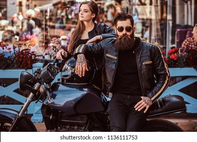 Attractive hipster couple - bearded brutal male in sunglasses dressed in a black leather jacket and his young sensual girl standing near, posing against terrace of cafe.