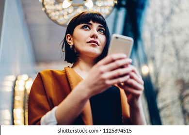 Attractive hipster girl holding smartphone device in hands and browsing wireless internet while pondering looking away, selective focus on caucasian beautiful woman with mobile phone indoors