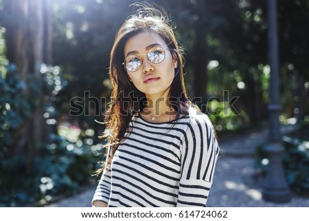 Attractive hipster girl with long dark hair wearing glasses is having rest while walking down the forest in a green zone on a sunny day. Asian woman is looking at the camera on the trees background.