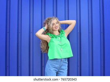 Attractive hipster girl posing near color wall