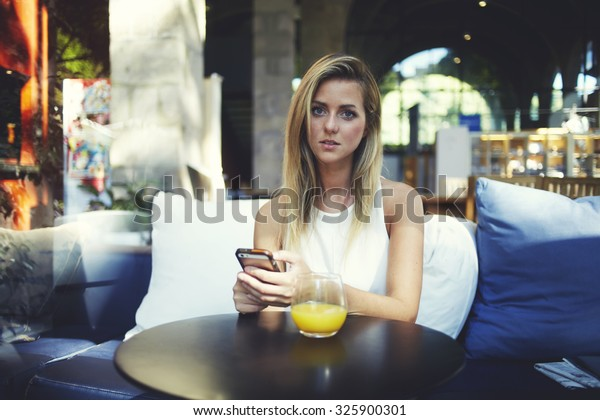 Attractive hipster girl waiting for a call on her mobile phone while enjoying rest in cozy coffee shop interior, beautiful caucasian woman posing while sitting with cell telephone in modern restaurant