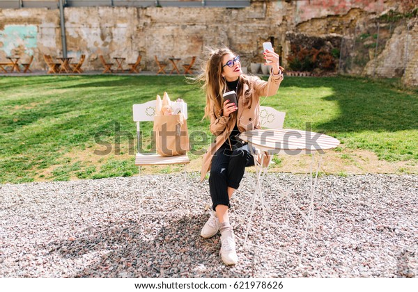 Attractive hipster girl wearing beige coat makes selfie fo  profile during coffee break in outdoor cafe. Young stylish woman taking pictures of herself in the park after food shopping