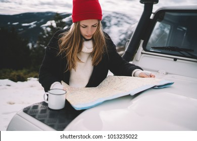 Attractive hipster girl wearing red knitted hat traveling in snowy mountains exploring map outdoor while drinking tea, beautiful tourist woman planning a route