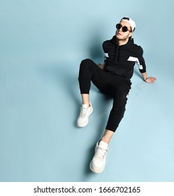 Attractive hipster man in cap, sunglasses, black tracksuit, bracelet and white sneakers. He is sitting on floor, looking aside, posing on blue background. Trendy outfit. Close up, top view, copy space