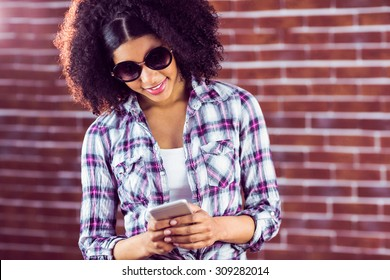 Attractive hipster with sunglasses texting against red brick background