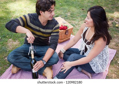 Attractive Hispanic Couple Having a Picnic Outdoors in the Park.
