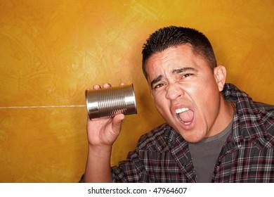 Attractive Hispanic man with tin can telephone