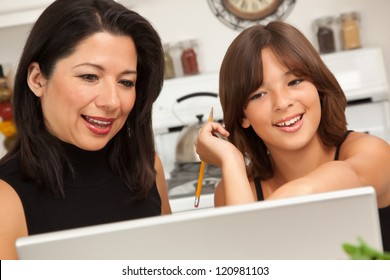 Attractive Hispanic Mother and Mixed Race Daughter in the Kitchen using the Laptop Computer Together.
