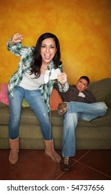 Attractive Hispanic woman playing video game while bored partner watches