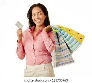 Attractive Hispanic woman wearing brightly colored clothes holding shopping bags and a credit card isolated on white background