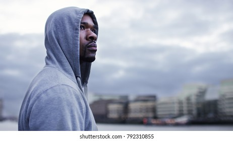 Attractive hooded male looking out across the city