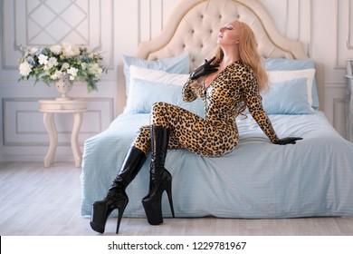 attractive hot blonde woman wearing leopard overall and black heels posing on the blue bed alone in her room