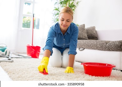 Attractive housewife cleaning carpet with brush and doing housework