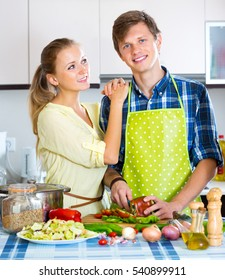 Attractive husband helping wife to prepare healthy dinner