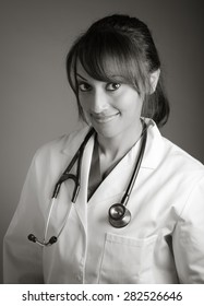 Attractive Indian doctor woman posing in a studio in front of a background, black and white image