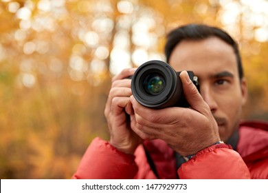 Attractive indian man taking pictures with a mirrorless camera through the forest in the fall in Canada