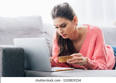 attractive indian woman with bindi shopping online with laptop and credit card