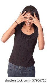 Attractive Indian woman holding her hands over her eyes, but looking through the fingers. On white background.