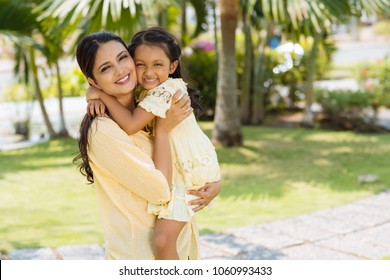 Attractive Indian woman looking at camera with toothy smile while holding her cute little daughter on arms, public park illuminated with sunbeams on background