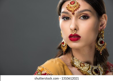 attractive indian woman posing in traditional bindi, isolated on grey