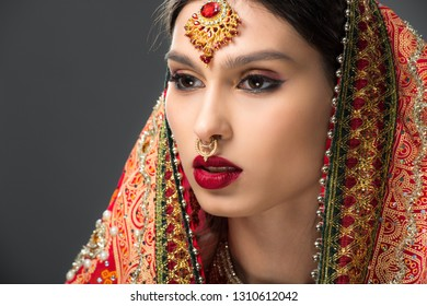 attractive indian woman posing in traditional sari and bindi, isolated on grey