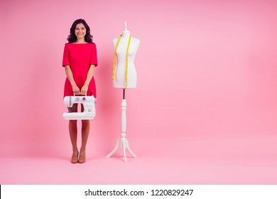 attractive indian woman seamstress tailor ( dressmaker) standing next to the mannequin with sewing machine on pink background in the studio copyspace . concept of idea and inspiration