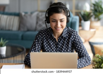 Attractive indian woman sit at homeoffice room wearing headset take part in educational webinar using laptop. Video call event with clients or personal chat with friend remotely concept