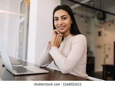 Attractive Indian woman using laptop computer for startup project, researching information online. Positive university student learning language, exam preparation. Online education concept.