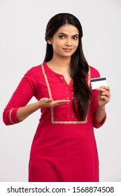 Attractive Indian young woman holding credit card on white.