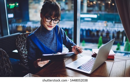 Attractive intelligent female manager of cafeteria checking list of necessary things to buy from folder while sitting at table with modern laptop computer, concept of distance job and technology