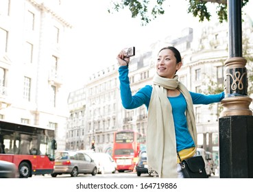 Attractive Japanese tourist woman sightseeing in a classic architecture street in the destination city of London, taking pictures with a digital photo camera during a sunny day on vacation, outdoors.
